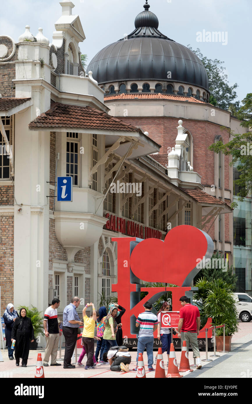 Tourists photographing 'I Love KL' city sign - Stock Image