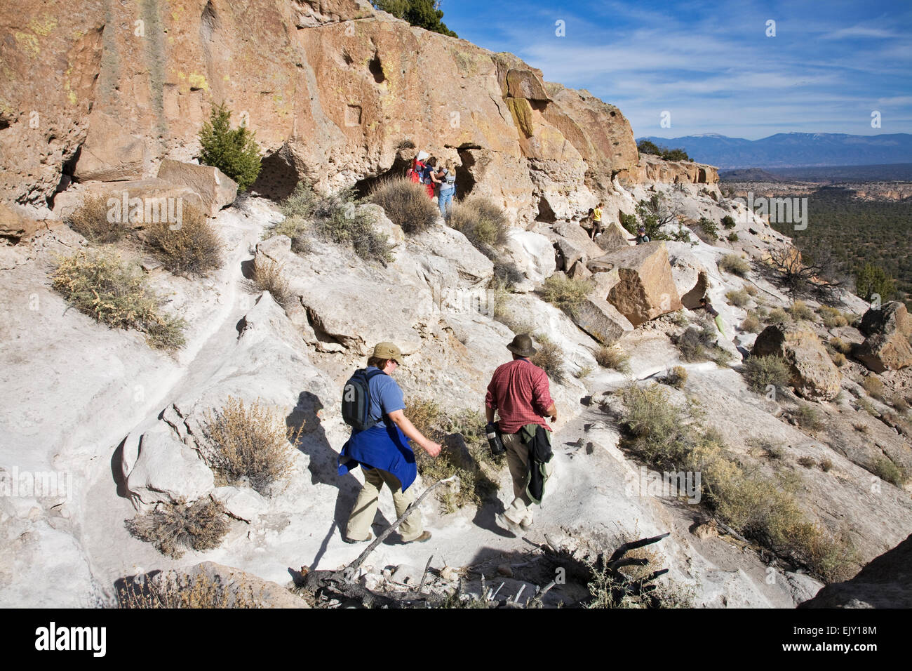 Hikers wander along the trail below the top of the mesa at Tsankawi, a part of Bandelier National Monument near - Stock Image
