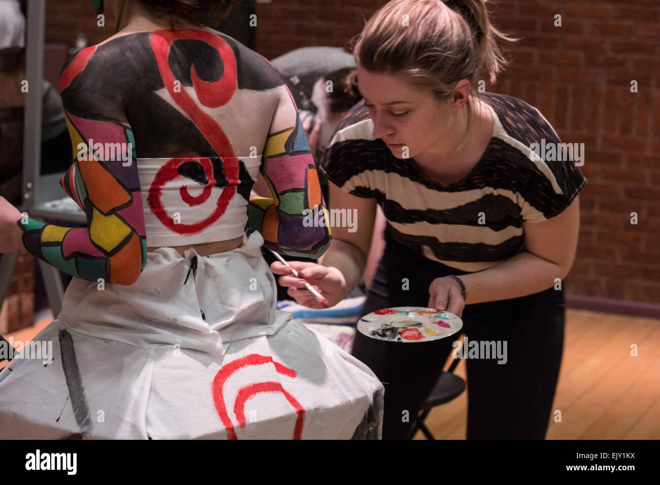 Woman putting final touches of body paint onto a female model in costume and face paint. - Stock Image