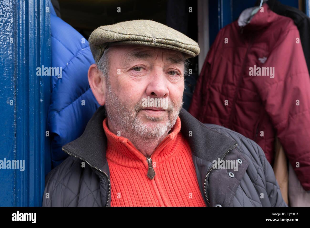 Secondhand clothes dealer outside his shop. Gallowgate, Glasgow, Scotland. - Stock Image
