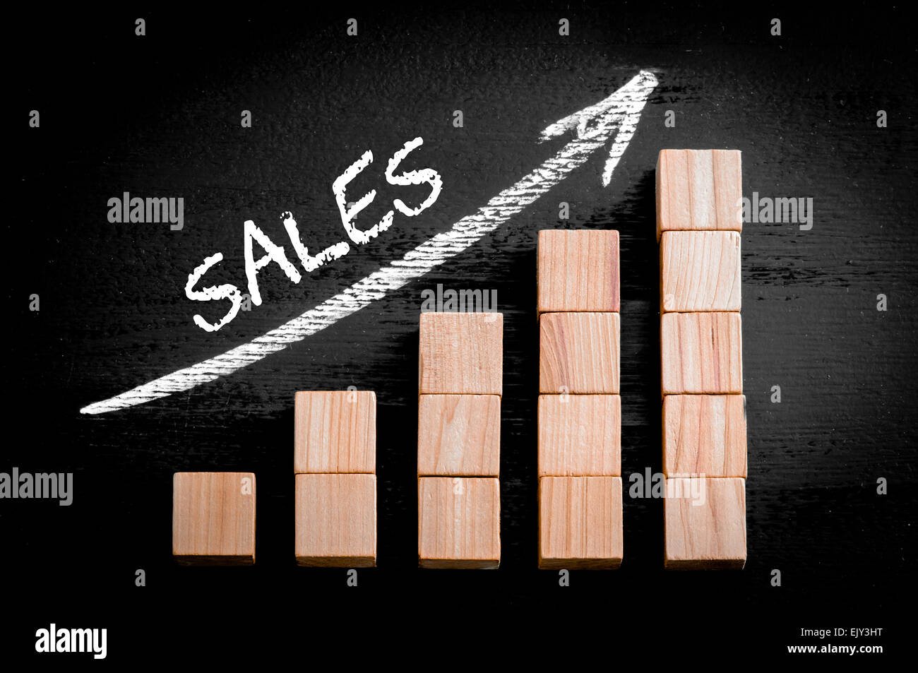 Word Sales on ascending arrow above bar graph of Wooden small cubes isolated on black background. Chalk drawing - Stock Image