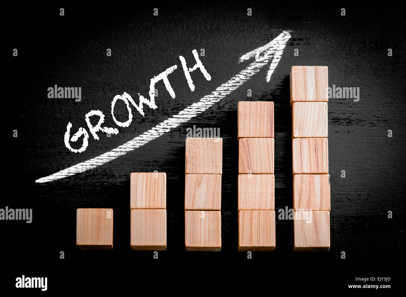 Word Growth on ascending arrow above bar graph of Wooden small cubes isolated on black background. Chalk drawing - Stock Image