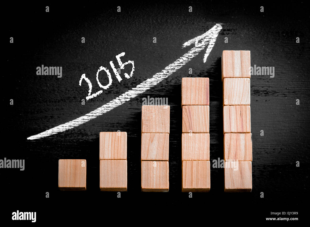 Year 2015 on ascending arrow above bar graph of Wooden small cubes isolated on black background. Chalk drawing on - Stock Image