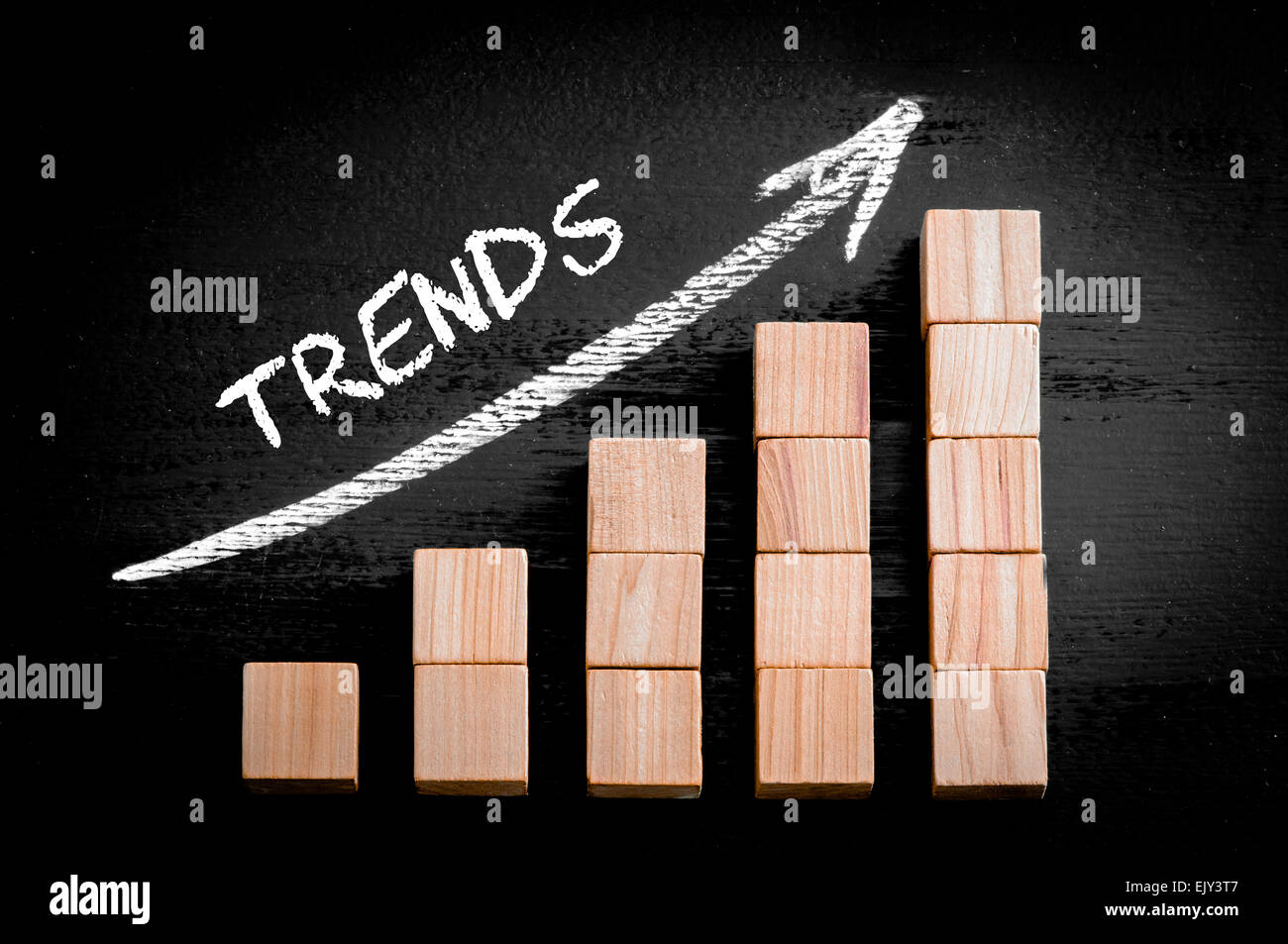 Word Trends on ascending arrow above bar graph of Wooden small cubes isolated on black background. Chalk drawing - Stock Image