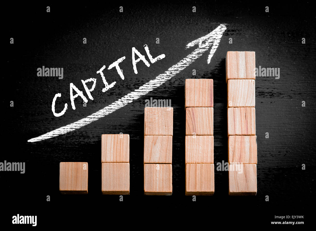 Word Capital on ascending arrow above bar graph of Wooden small cubes isolated on black background. Chalk drawing - Stock Image