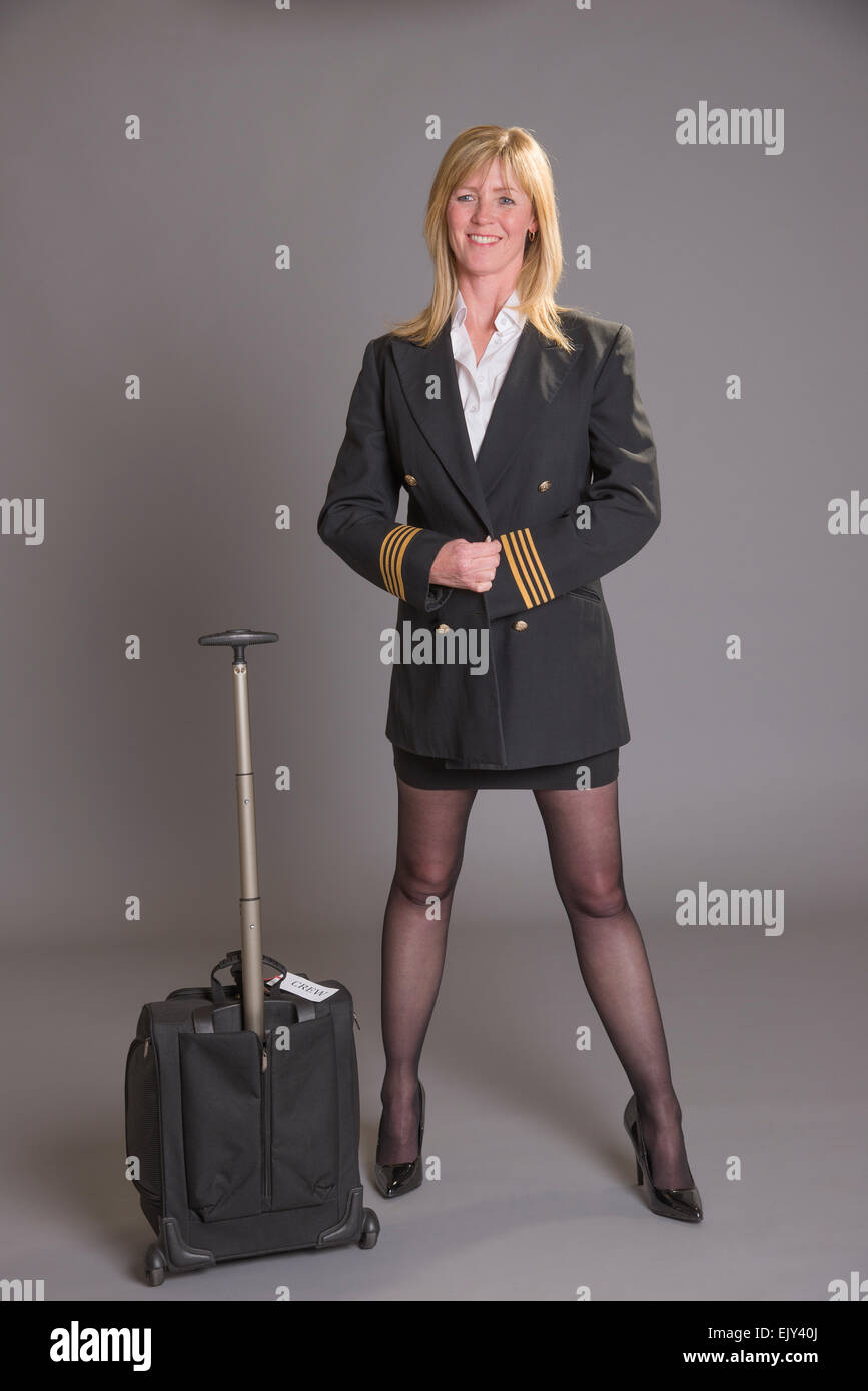 Female pilot in uniform standing in a short skirt fastening her jacket - Stock Image