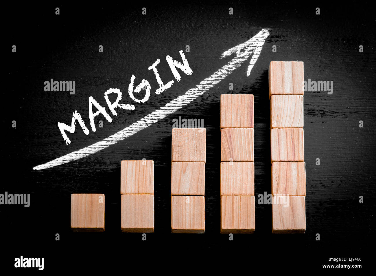 Word Margin on ascending arrow above bar graph of Wooden small cubes isolated on black background. Chalk drawing - Stock Image