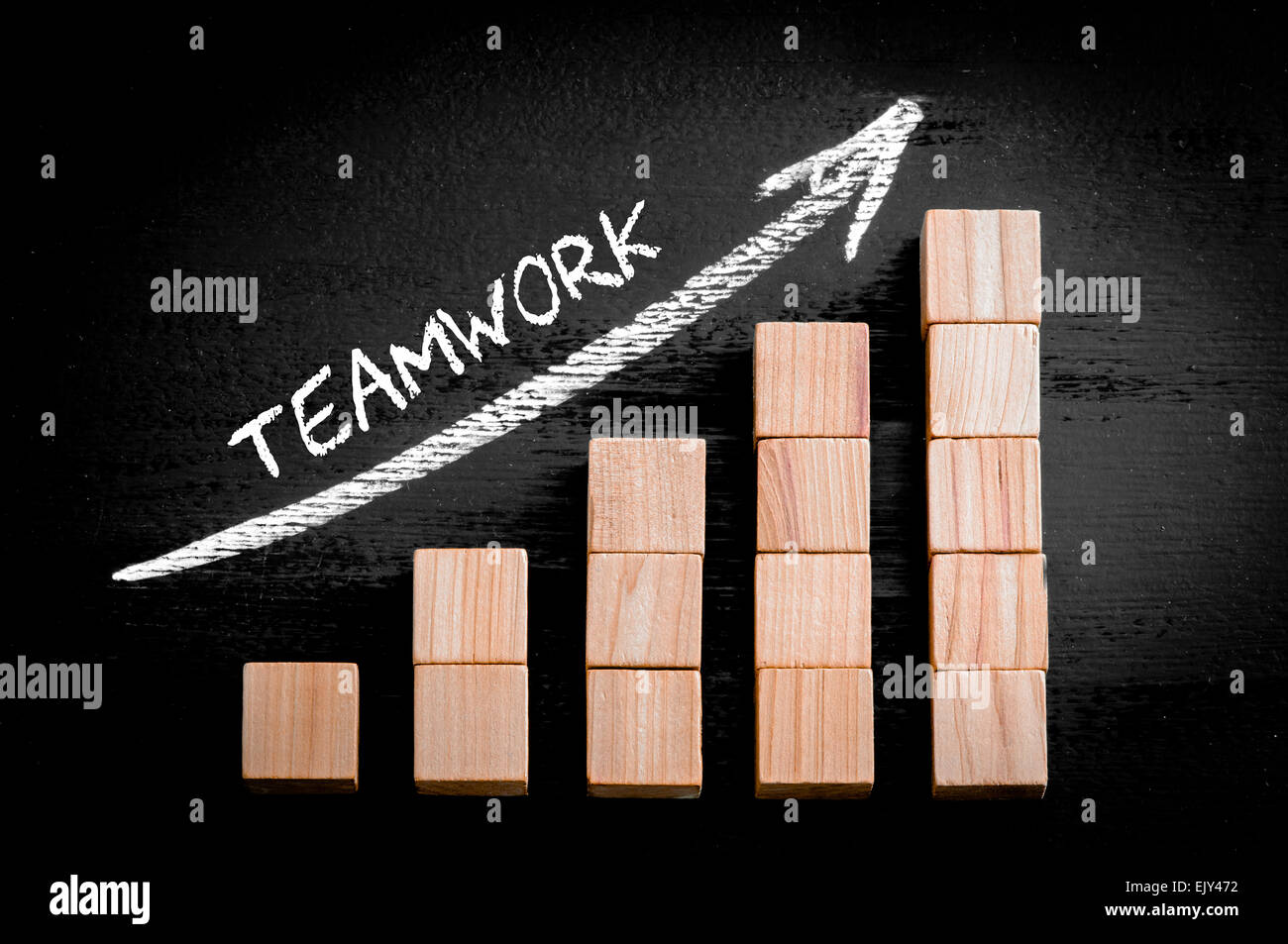 Word Teamwork on ascending arrow above bar graph of Wooden small cubes isolated on black background. Chalk drawing - Stock Image