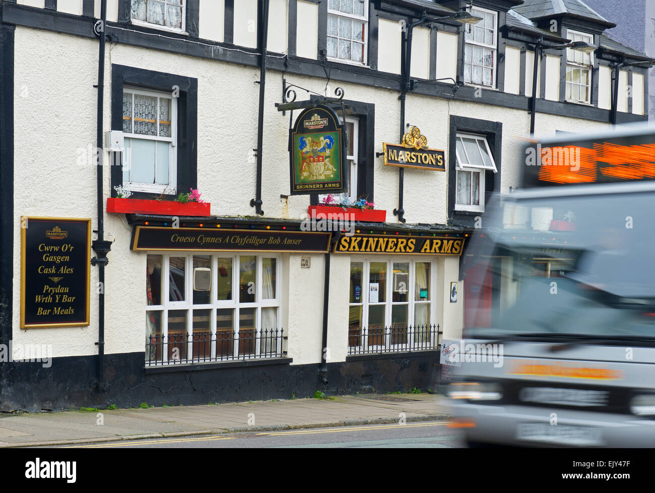 Blurred Royal Mail van passing the Skinners arms pub in Machynlleth, Powys, North Wales UK - Stock Image