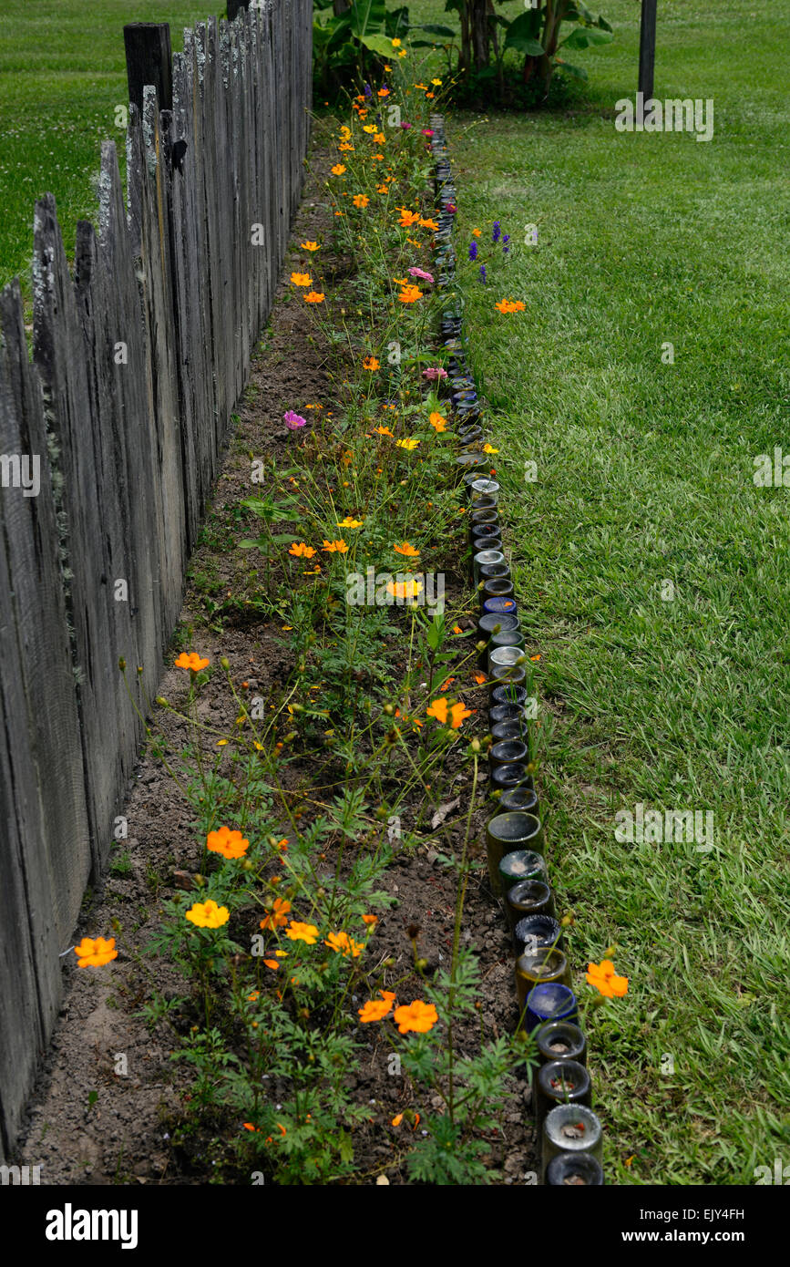 Wine bottles used use for flower bed border garden gardening different novel eccentric usage recycle recycling RM - Stock Image