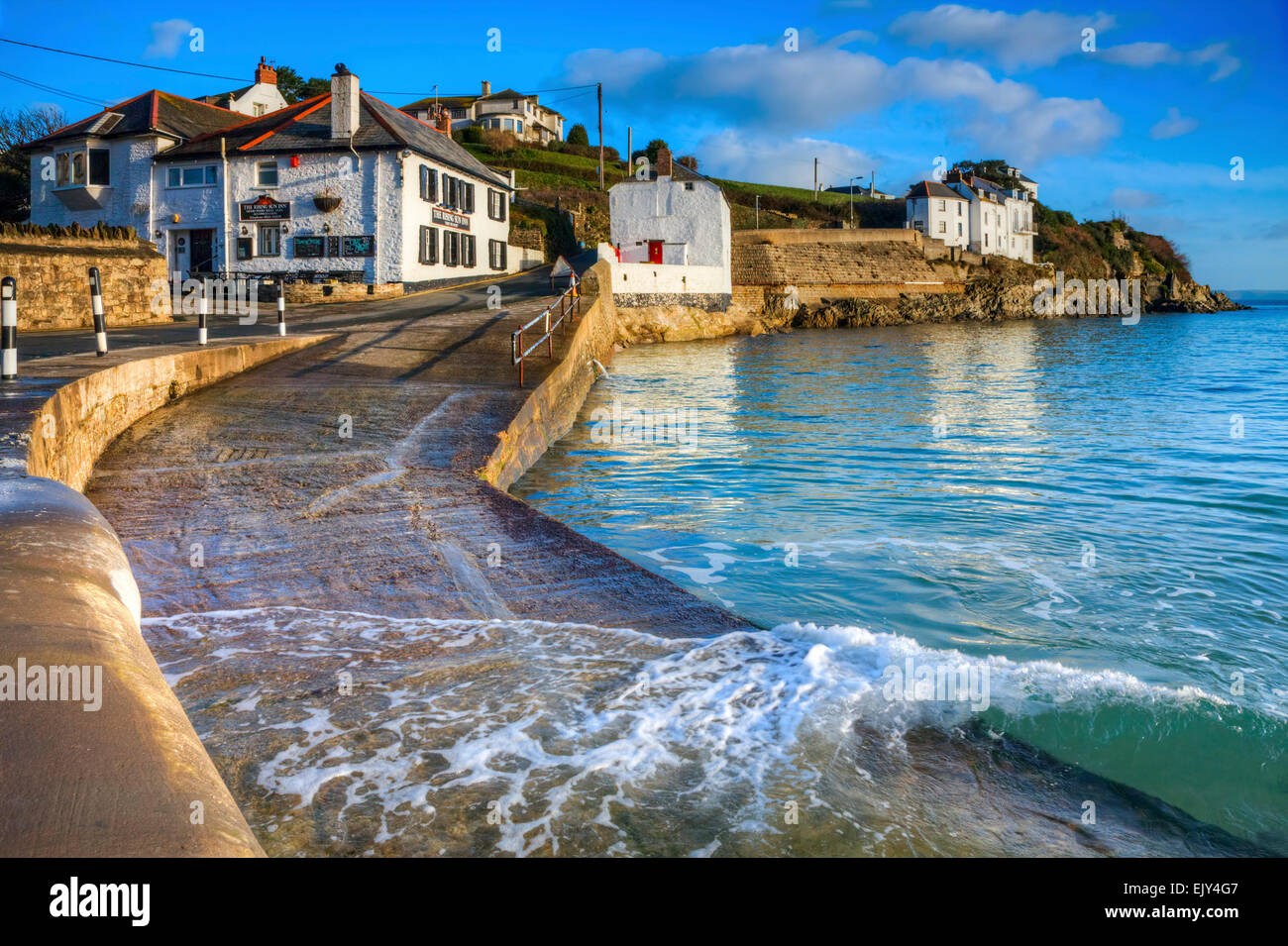 The slipway at Portmellon near Mevagissey in Cornwall, with The Rising Sun Inn in the distance. - Stock Image