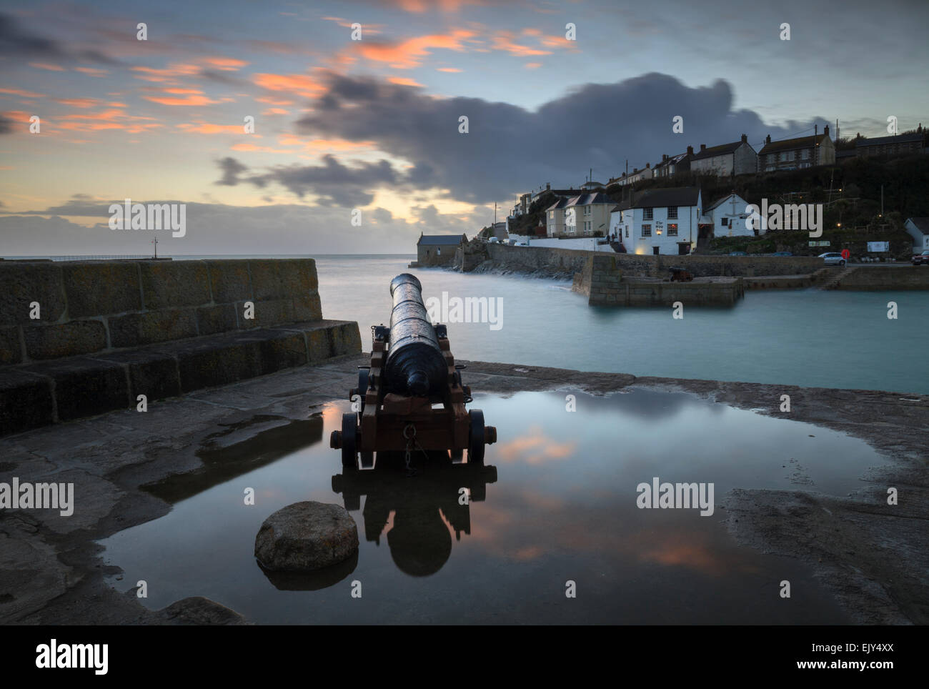 A Canon at the entrance to the harbour at Porthleven on Cornwall's Lizard Peninsular, reflected in a large pool - Stock Image