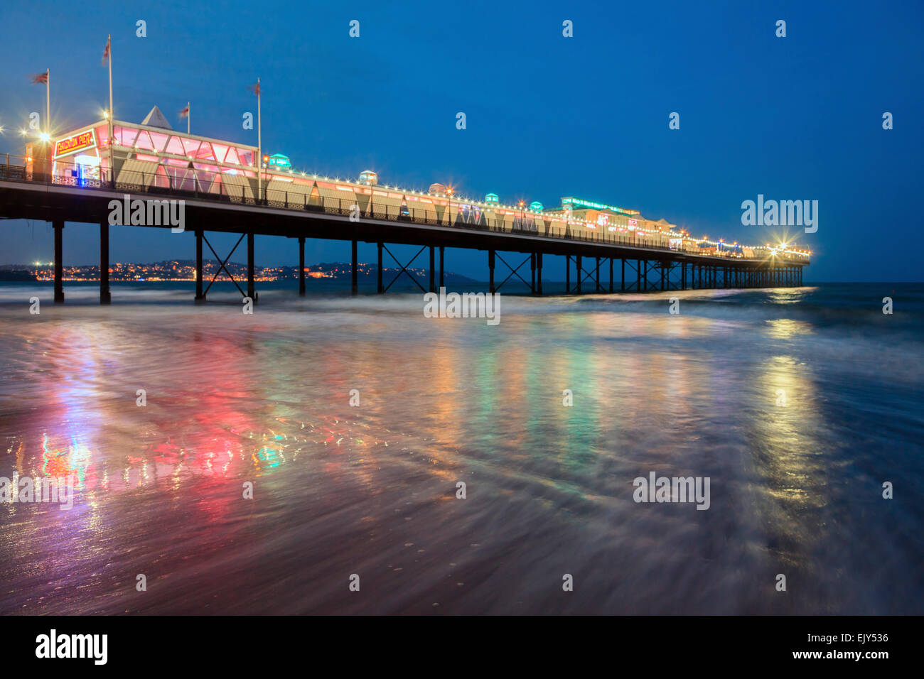Paignton Pier in Torbay, captured during the hours of twilight. - Stock Image