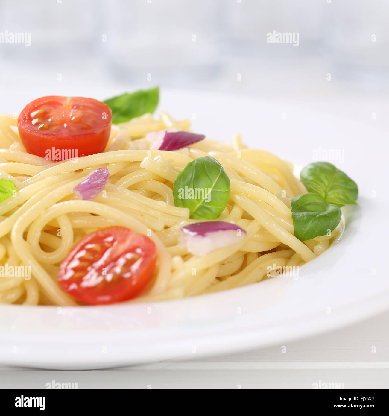 Italian cuisine spaghetti with tomatoes and basil noodles pasta on a plate - Stock Image