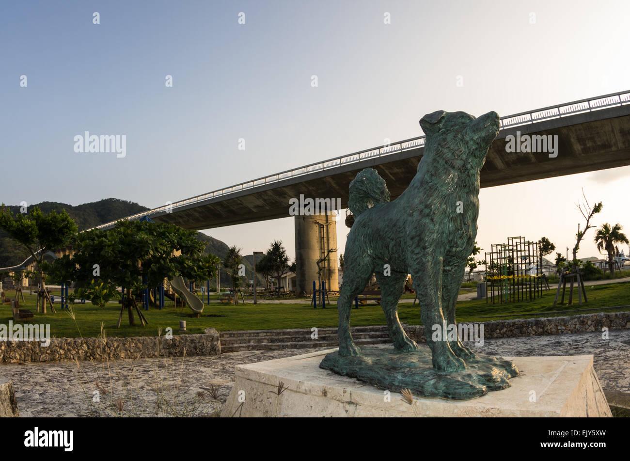 Statue of Shiro the Dog on Aka Island with bridge connecting to Geruma Island in the background, Keramas, Okinawa, Stock Photo
