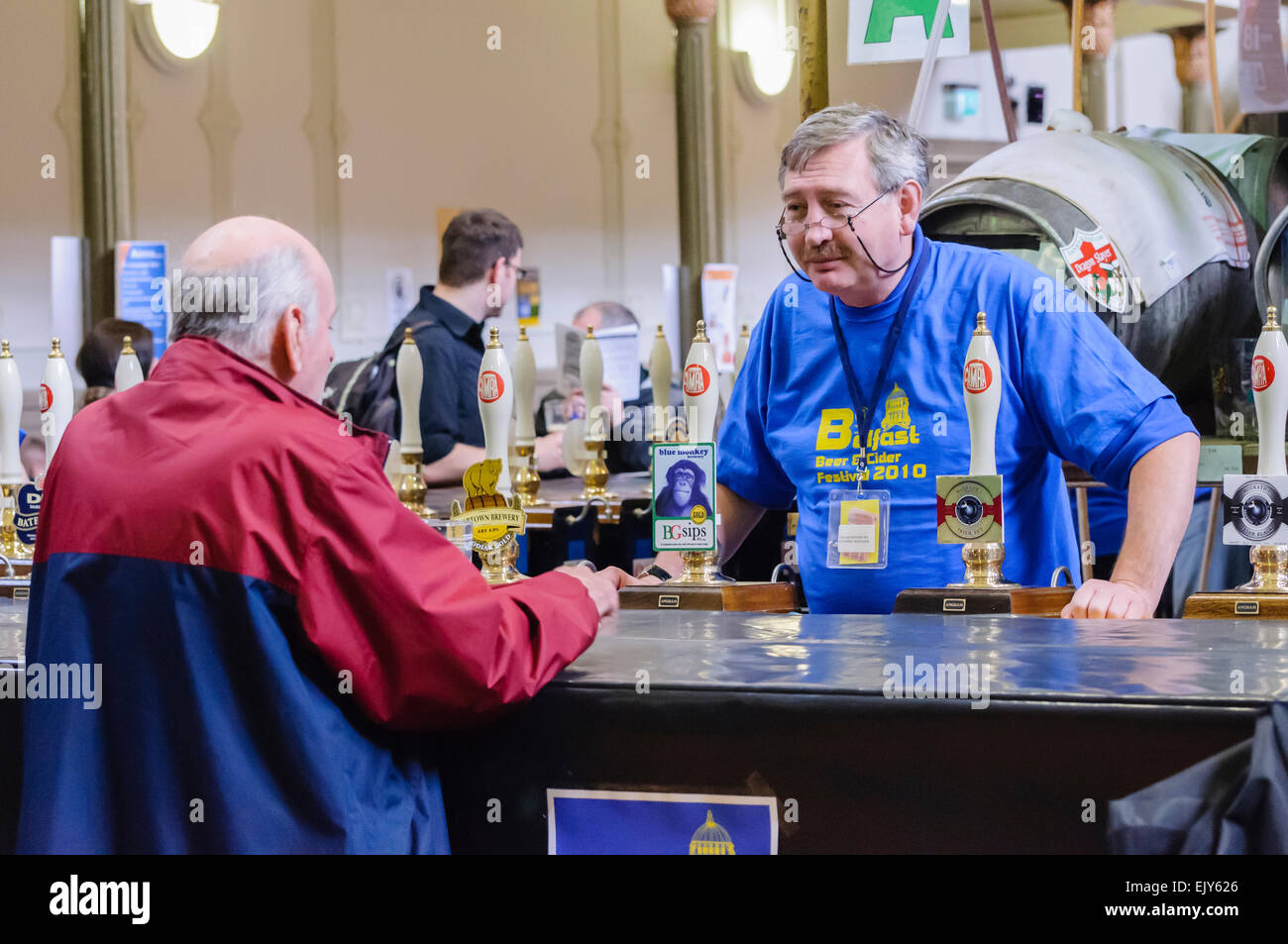 A barman serves customers at a CAMRA real ale festival. - Stock Image