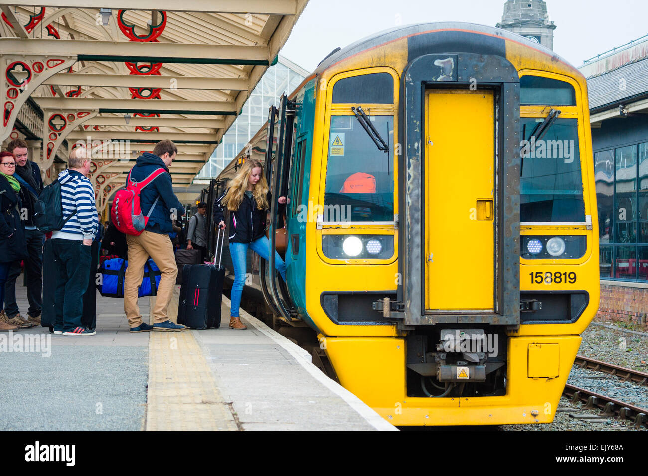 Public transport: University Students  going home boarding an Arriva Wales train at Aberystwyth railway station - Stock Image