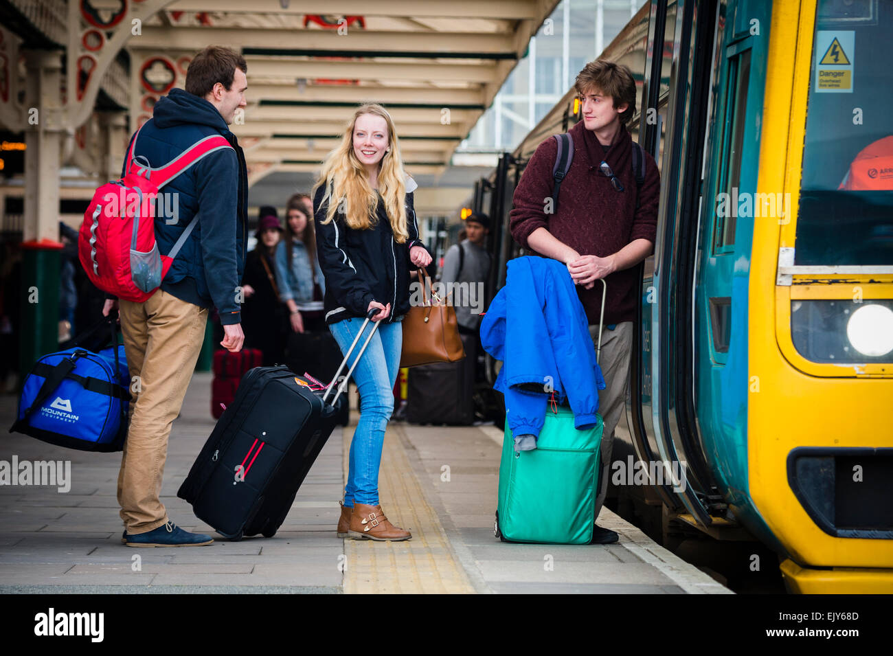 Public transport: University Students with their luggage going home catching an Arriva Wales train on the platform - Stock Image