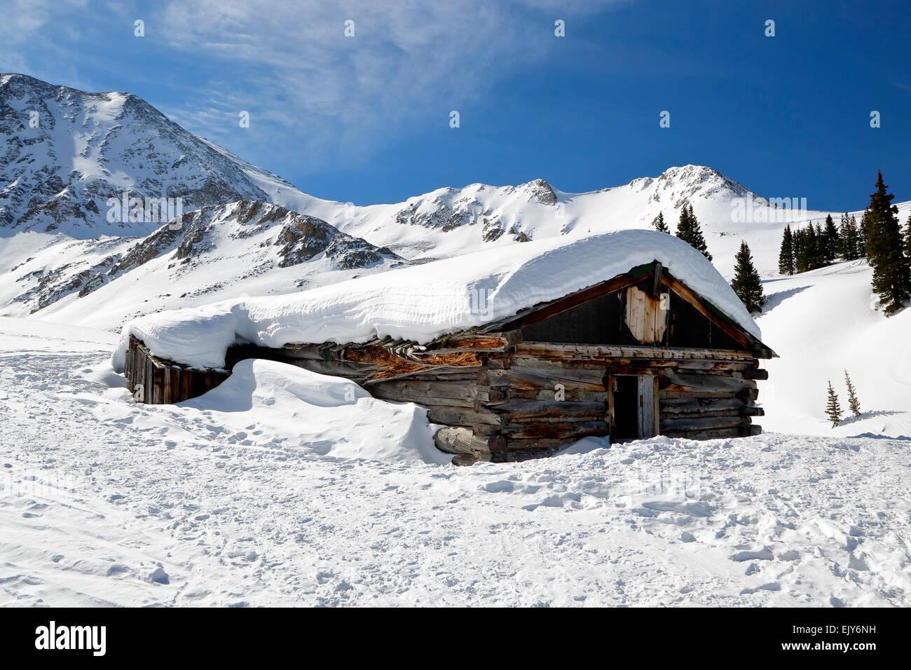 Snow-covered Ten-Mile Range and ruined log cabin, Boston Mine, Mayflower Gulch, near Copper Mountain, Colorado USA - Stock Image