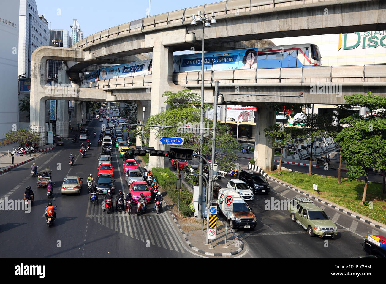 Street scene showing rush hour traffic and BTS train on tracks coming into Siam BTS station in Bangkok, Thailand - Stock Image