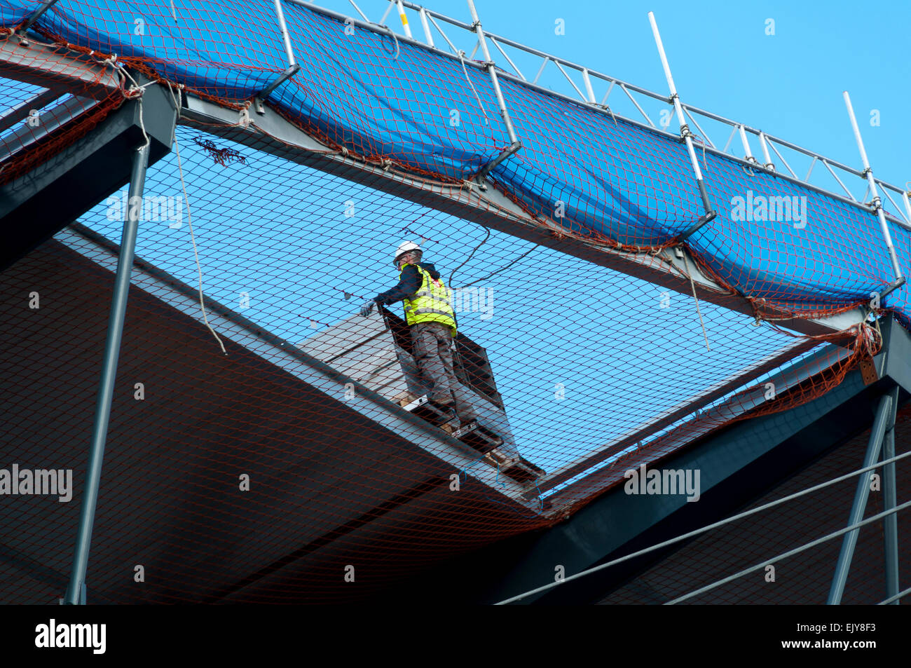 Workman Above Safety Netting On The Roof Of The Etihad