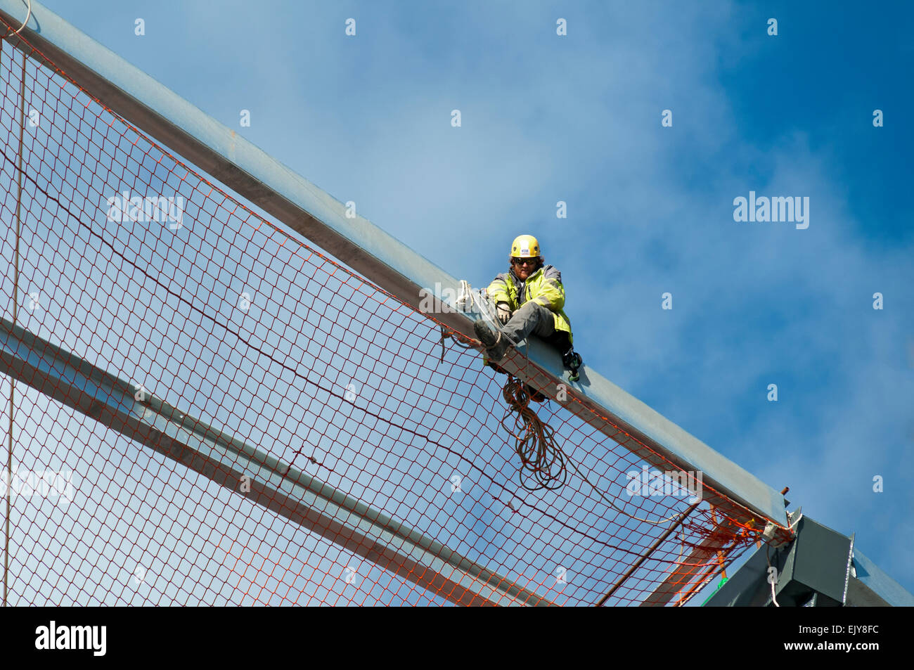 Workman fixing safety netting on the roof of the Etihad Stadium, South Stand expansion project, Manchester, England, - Stock Image