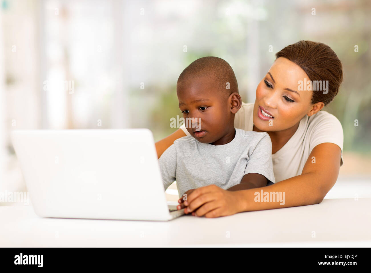 adorable little African boy using laptop with his mother at home - Stock Image