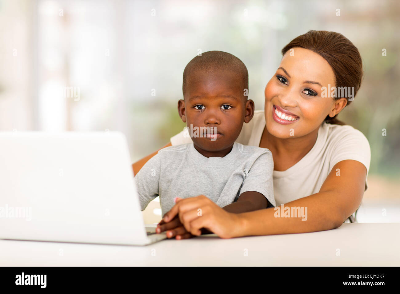 happy African woman relaxing at home with her little boy - Stock Image