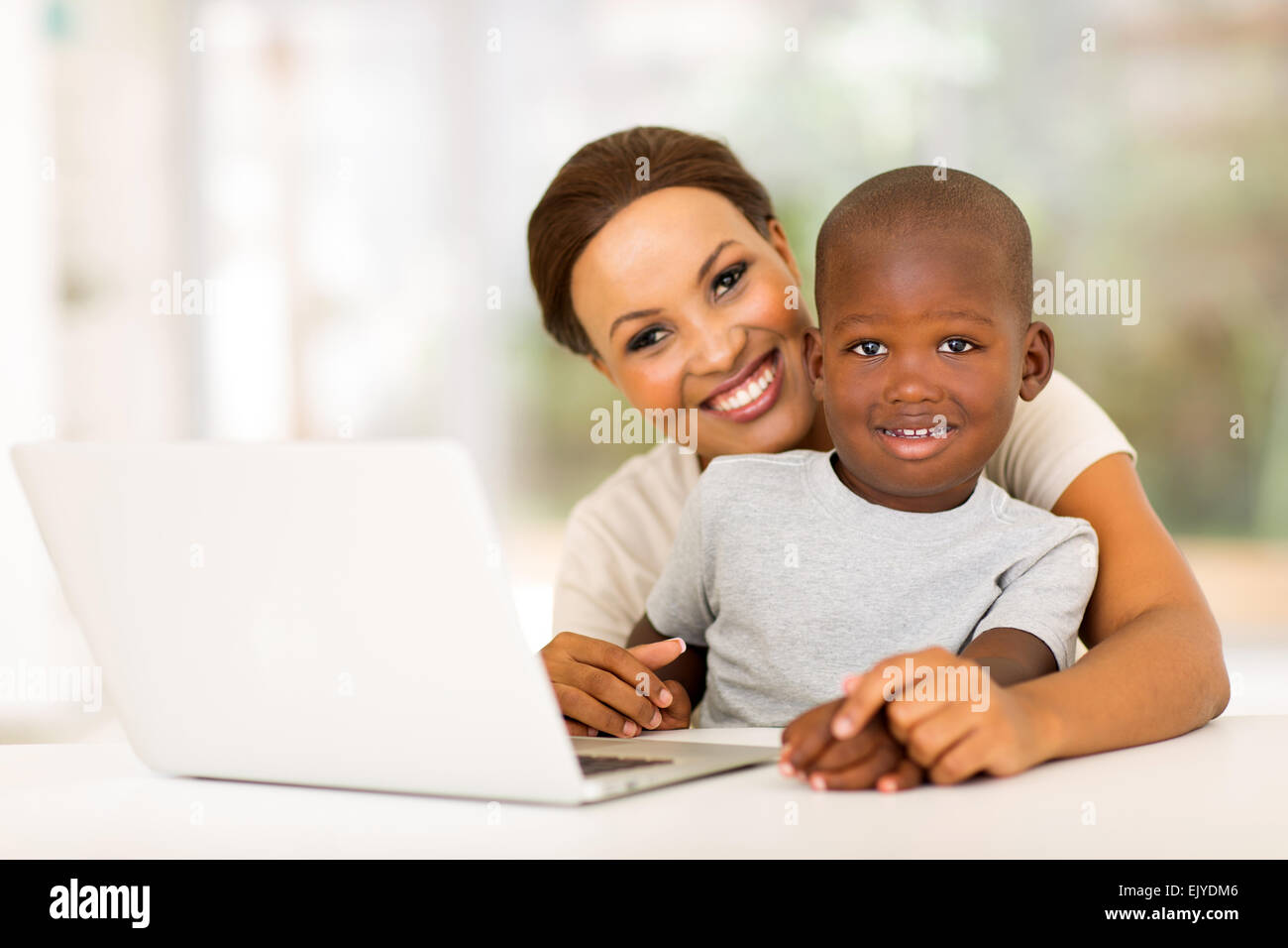 cute little boy and mother with laptop computer at home - Stock Image