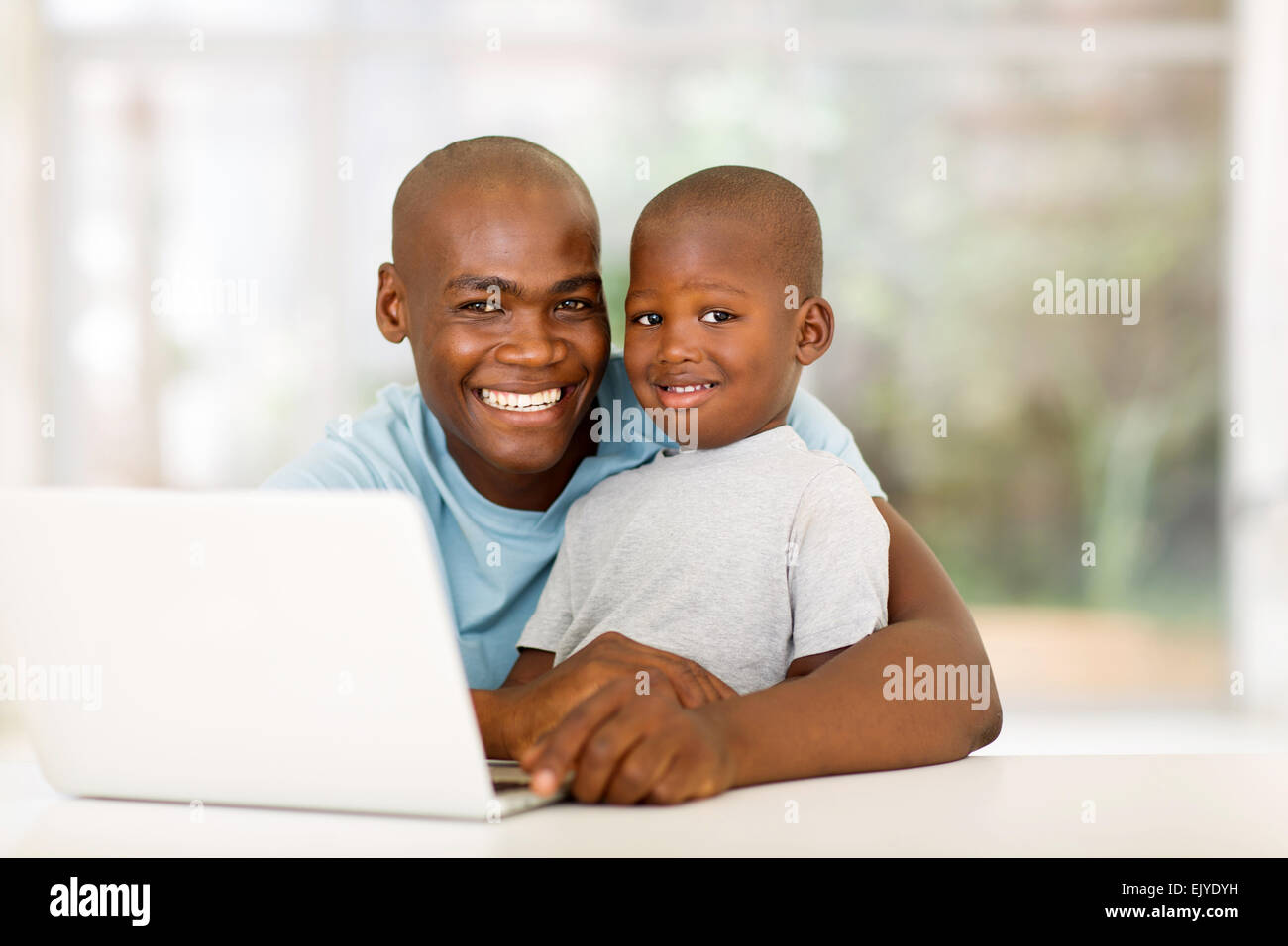 handsome young African man relaxing at home with his little boy - Stock Image