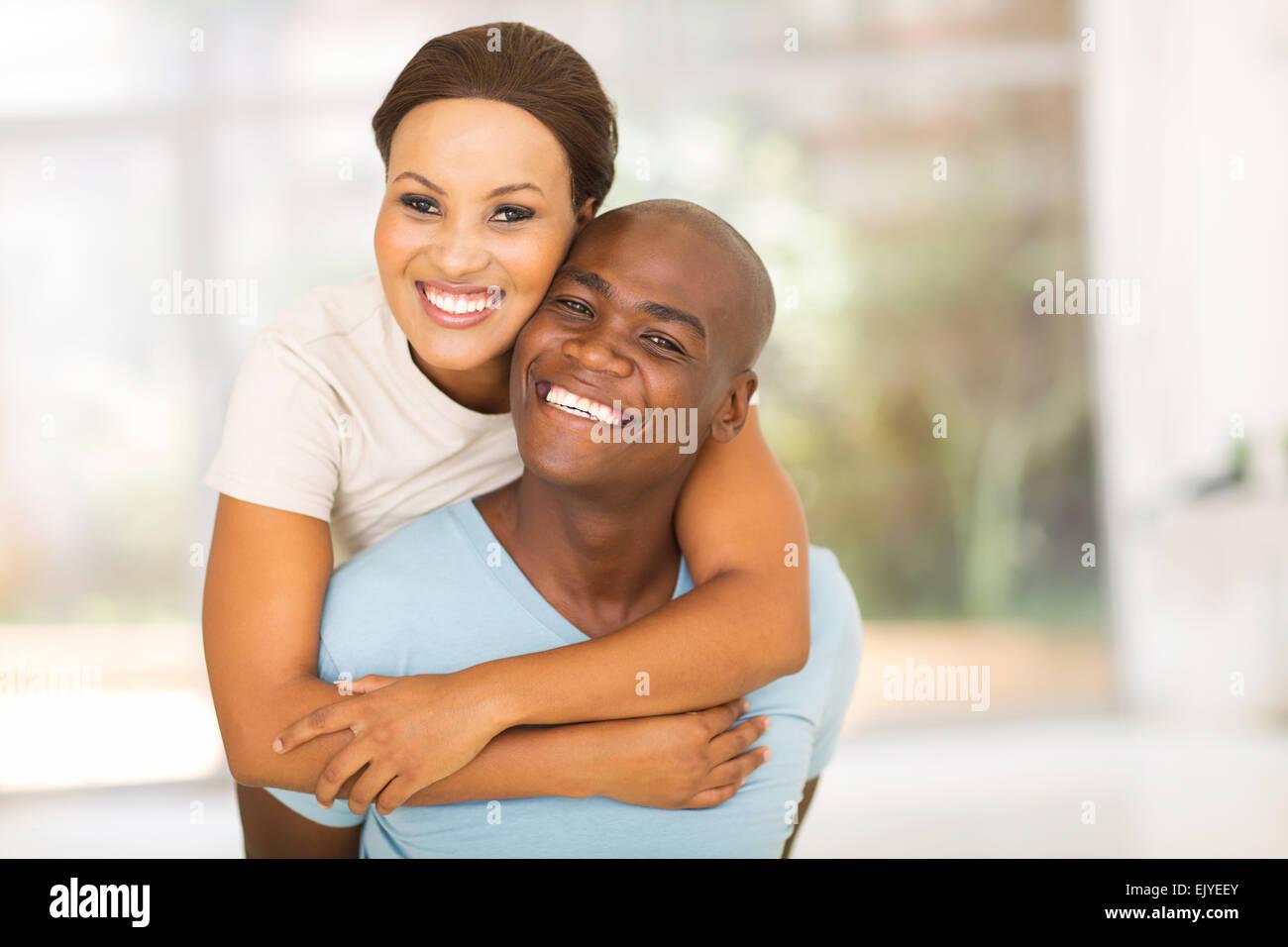 happy African woman enjoying piggyback ride on boyfriend - Stock Image