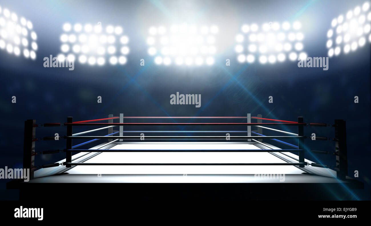 An boxing ring surrounded by ropes spotlit by floodlights in an arena setting at night - Stock Image