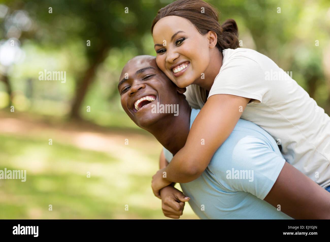 cheerful black woman enjoying piggyback ride on boyfriends back outdoors - Stock Image