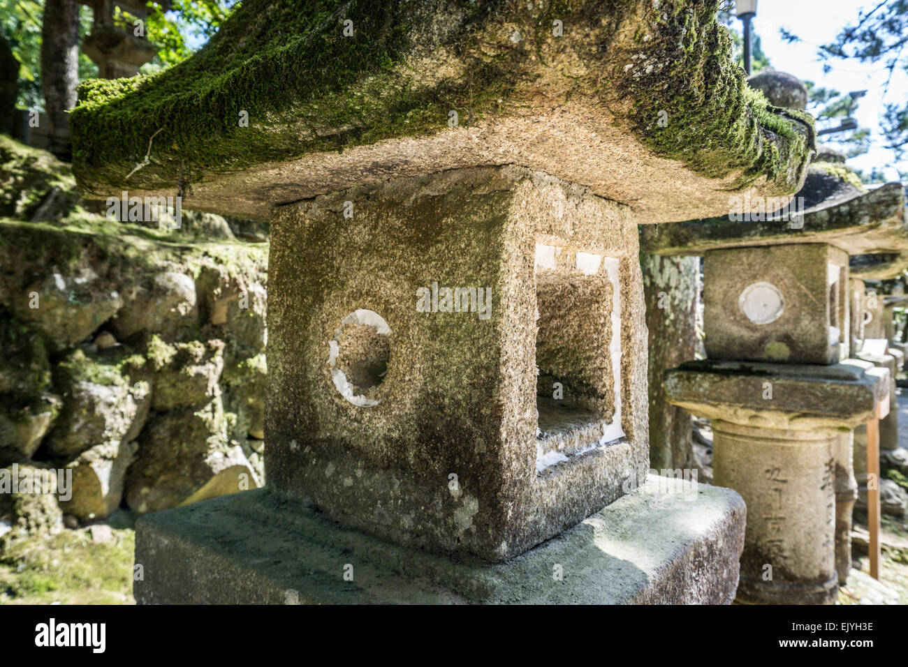 Close up view of two ancient Japanese stone lanterns in the forest near Kasuga Grand Shrine, Nara, Japan - Stock Image