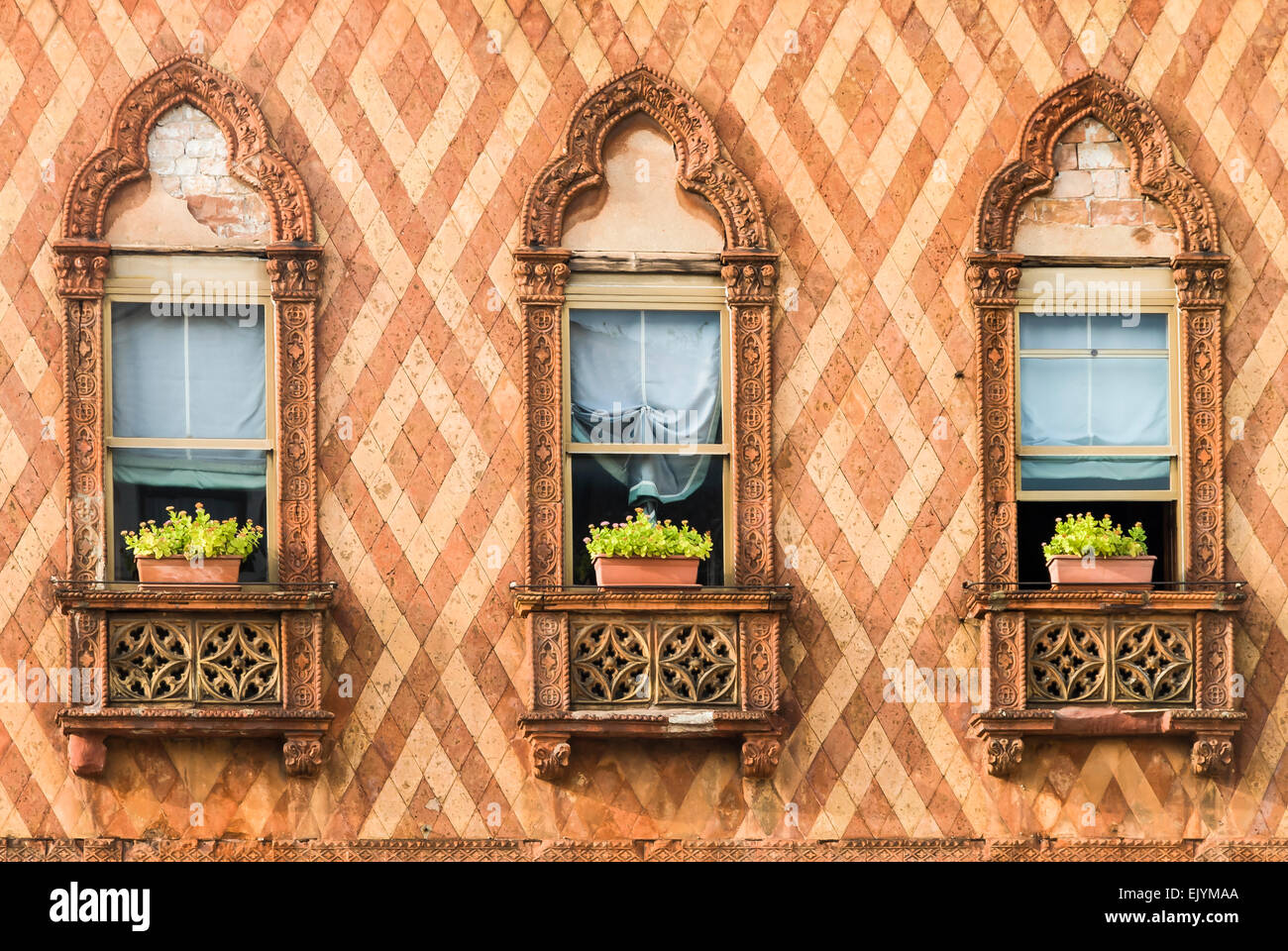 A trio of decorative Venetian windows surrounded by ornate brickwork - Stock Image