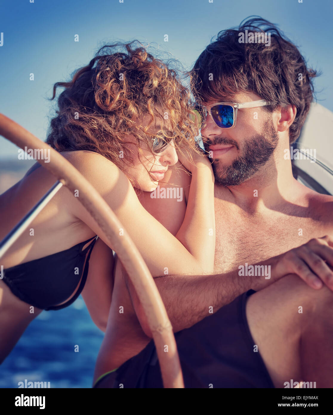 Portrait of a cute happy couple sitting on sailboat and enjoying bright summer day, enjoying romantic honeymoon - Stock Image