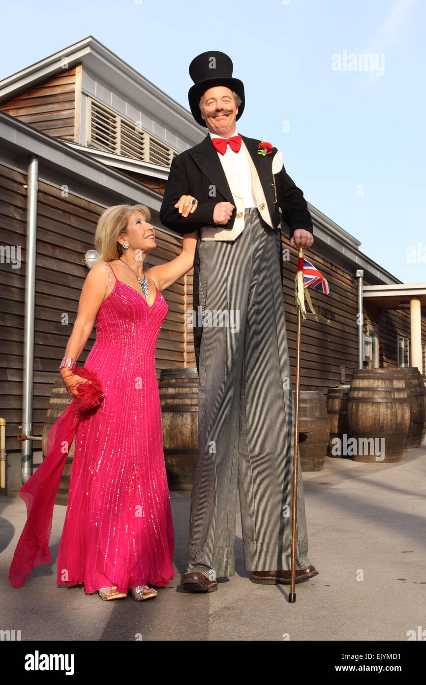 TV celebrity Jennie Bond stands alongside a man on stilts dressed as Brunel at an corporate evening event in Bristol - Stock Image