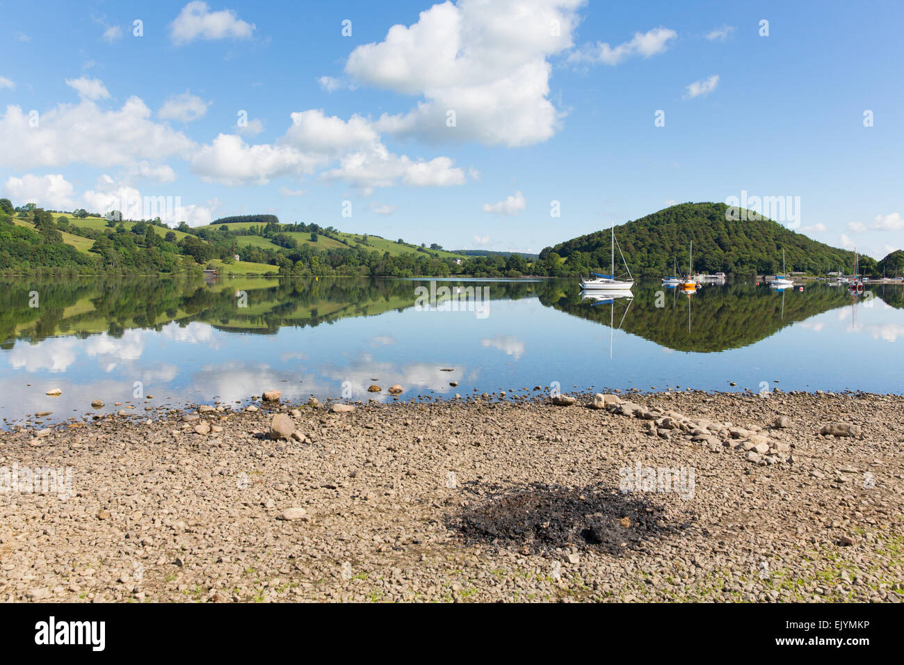Barbecue ashes by beautiful lake on calm idyllic summer morning with cloud reflections and blue sky Ullswater Lake Stock Photo