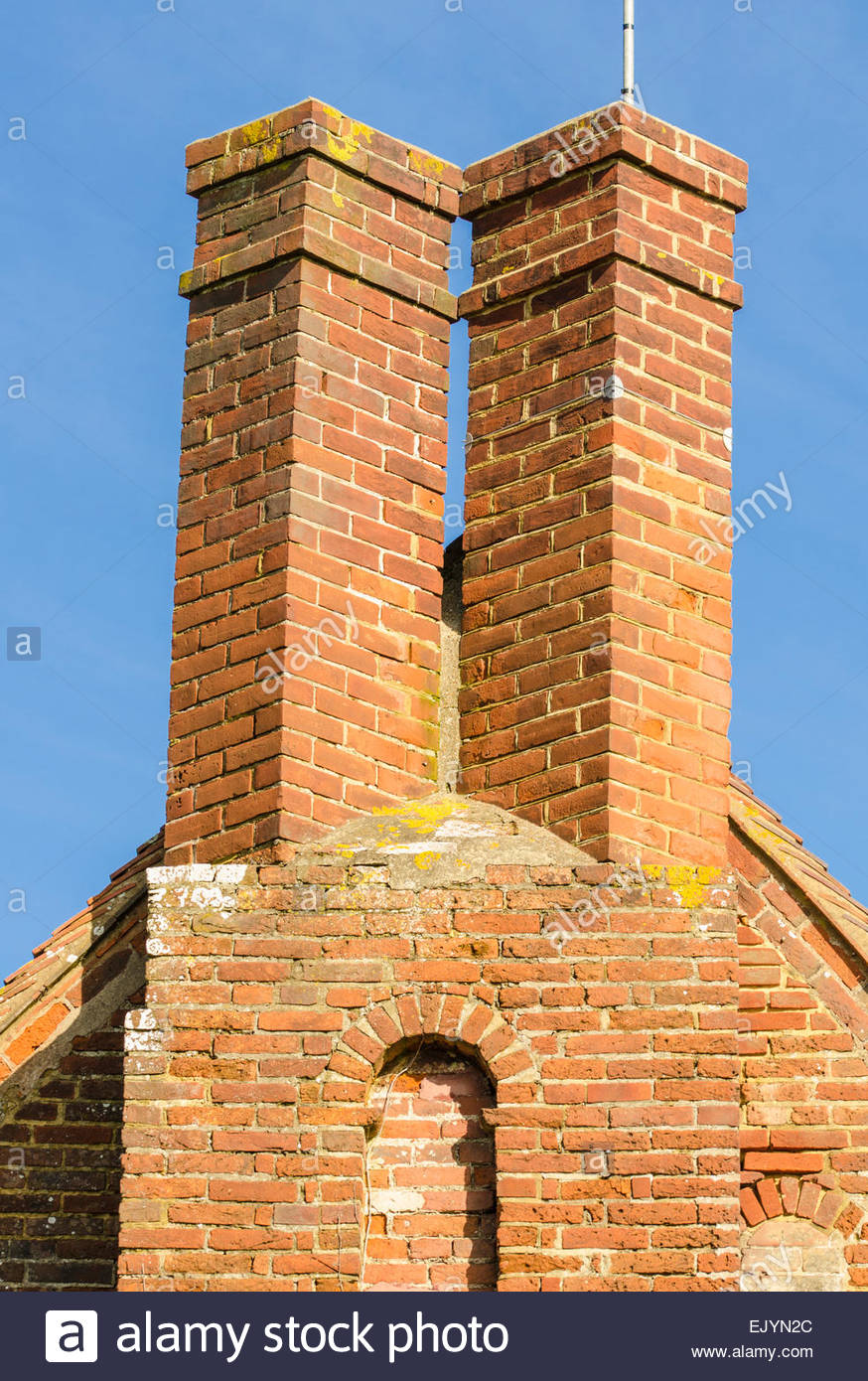 Tall twin red brick chimney stacks. - Stock Image