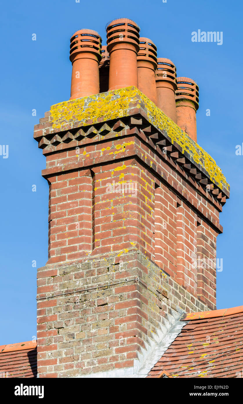 Red brick chimney stack with several pots and cowls, attached to a tiled roof. - Stock Image