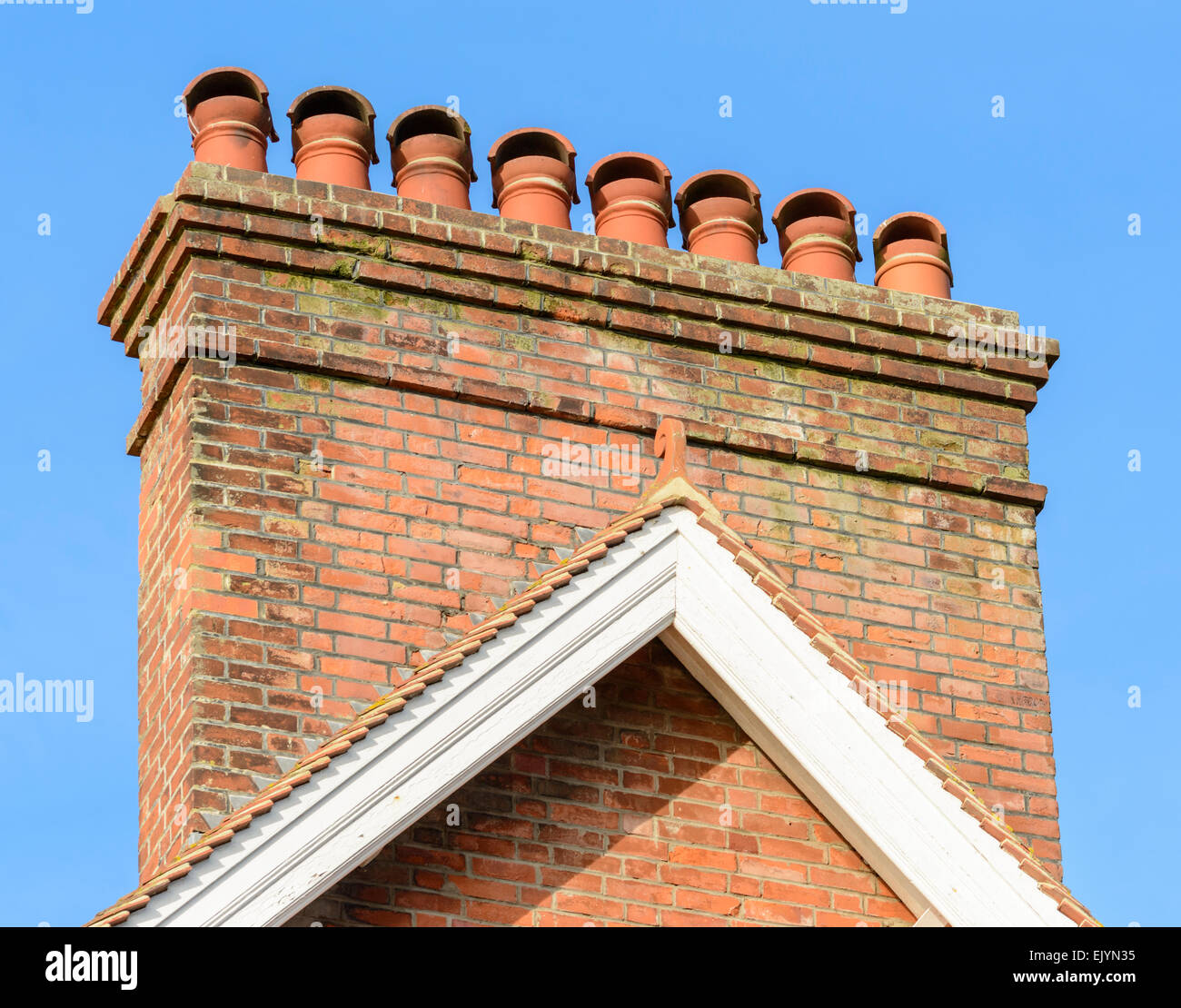 Chimney stack with 8 red chimney pots against blue sky. - Stock Image