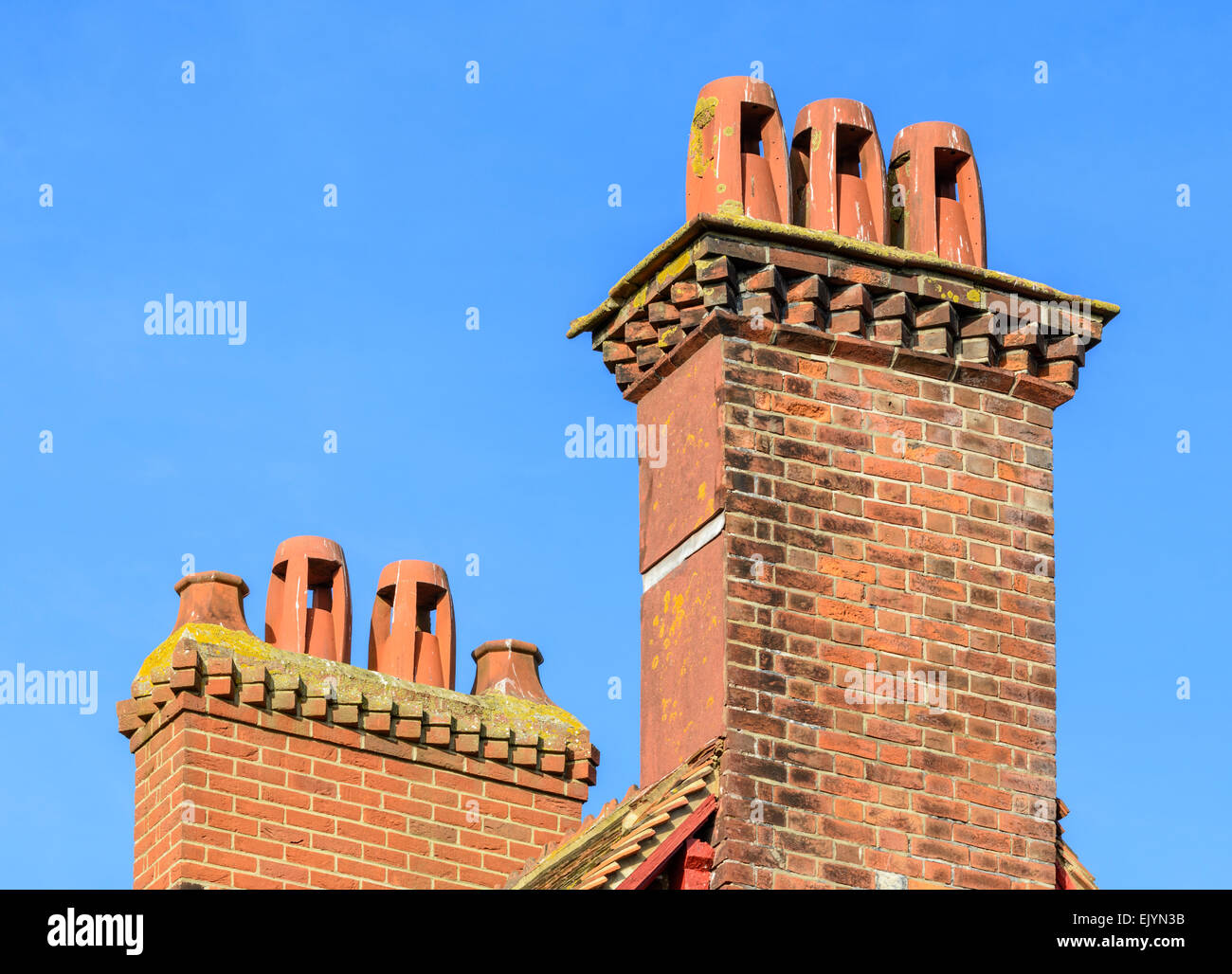 2 red brick chimney stacks with red chimney pots against blue sky in England, UK. - Stock Image
