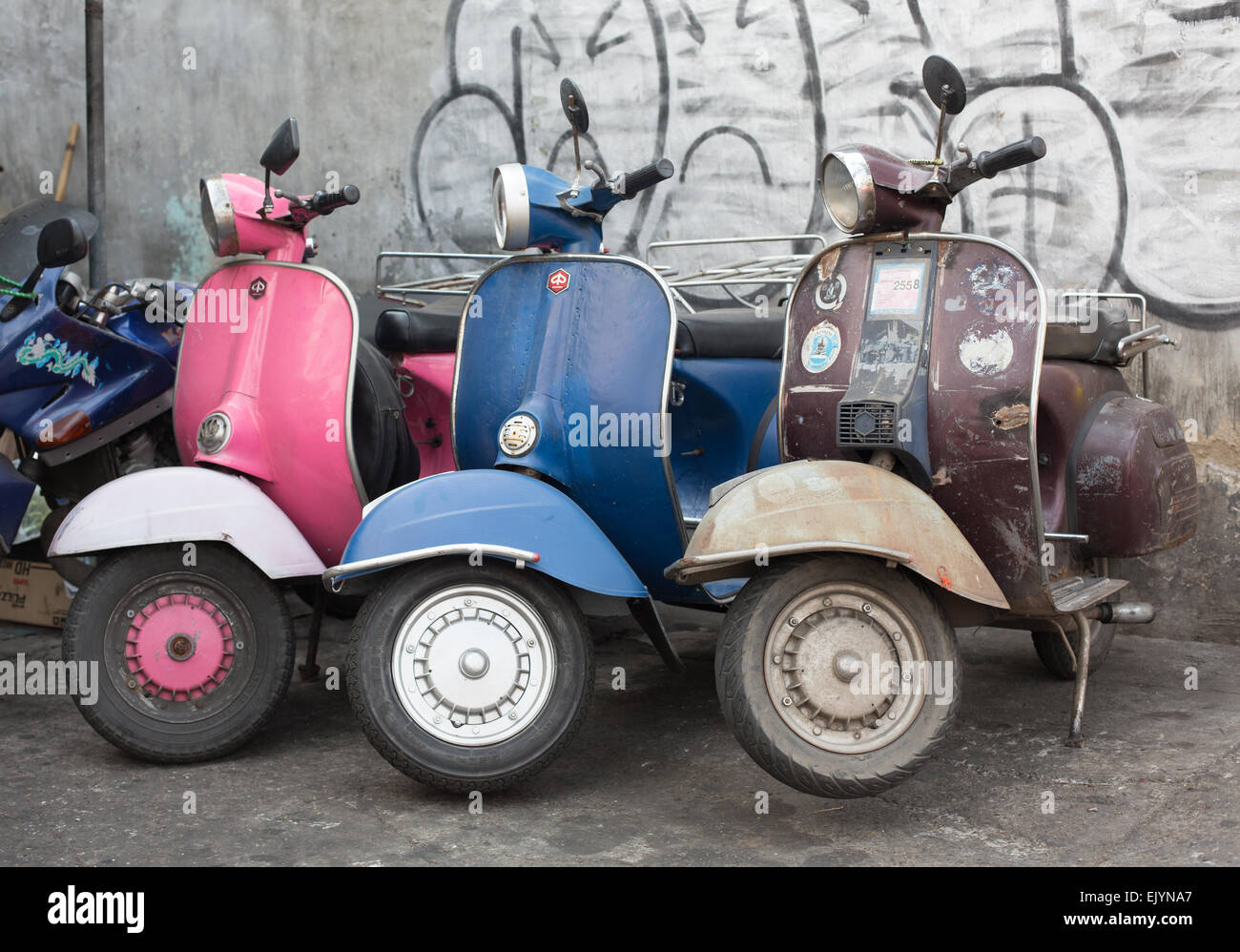 Three vintage vespa's of various colours lined up in front of a