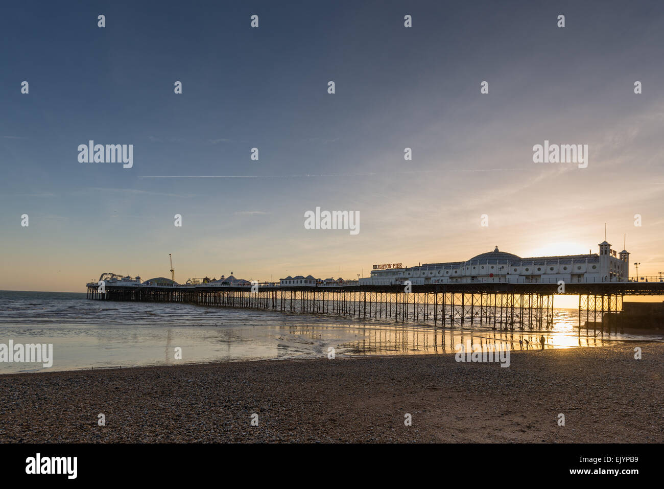 Brighton Pier at low tide during sunset - Stock Image