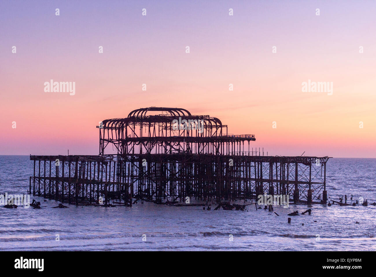 Brighton's skeletal West Pier at sunset with a largely clear brightly colored sky - Stock Image