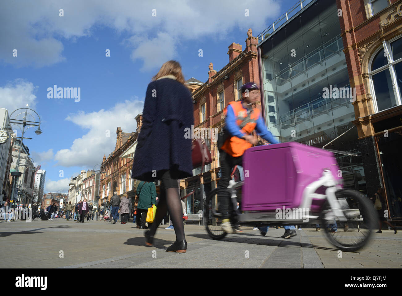 cycling courier delivering parcels by people shopping on briggate by harvey nichols leeds united kingdom - Stock Image