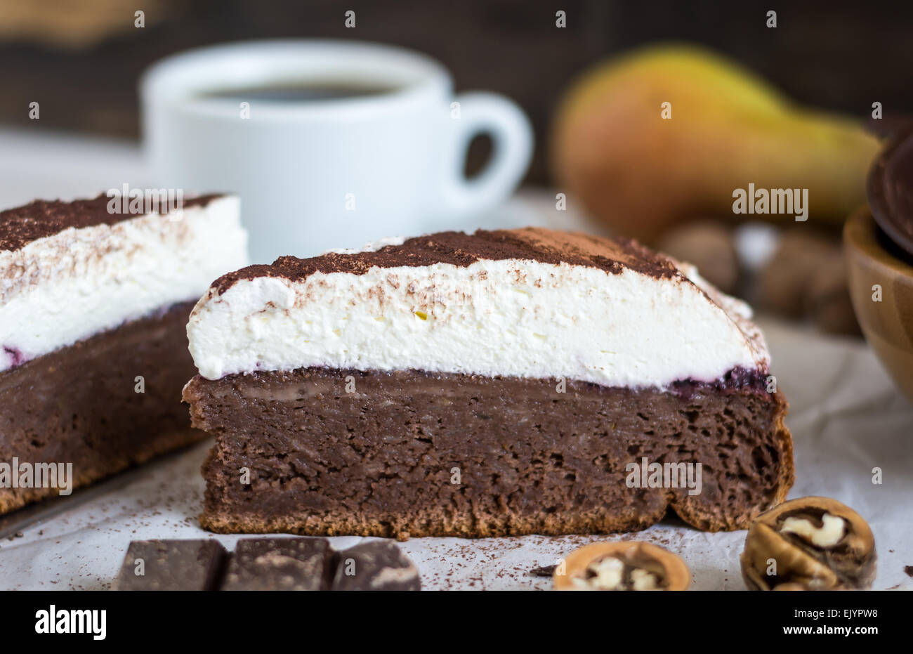 Chocolate Cake with Whipped Cream Dusted with Cocoa and Cup of Coffee Close Up - Stock Image