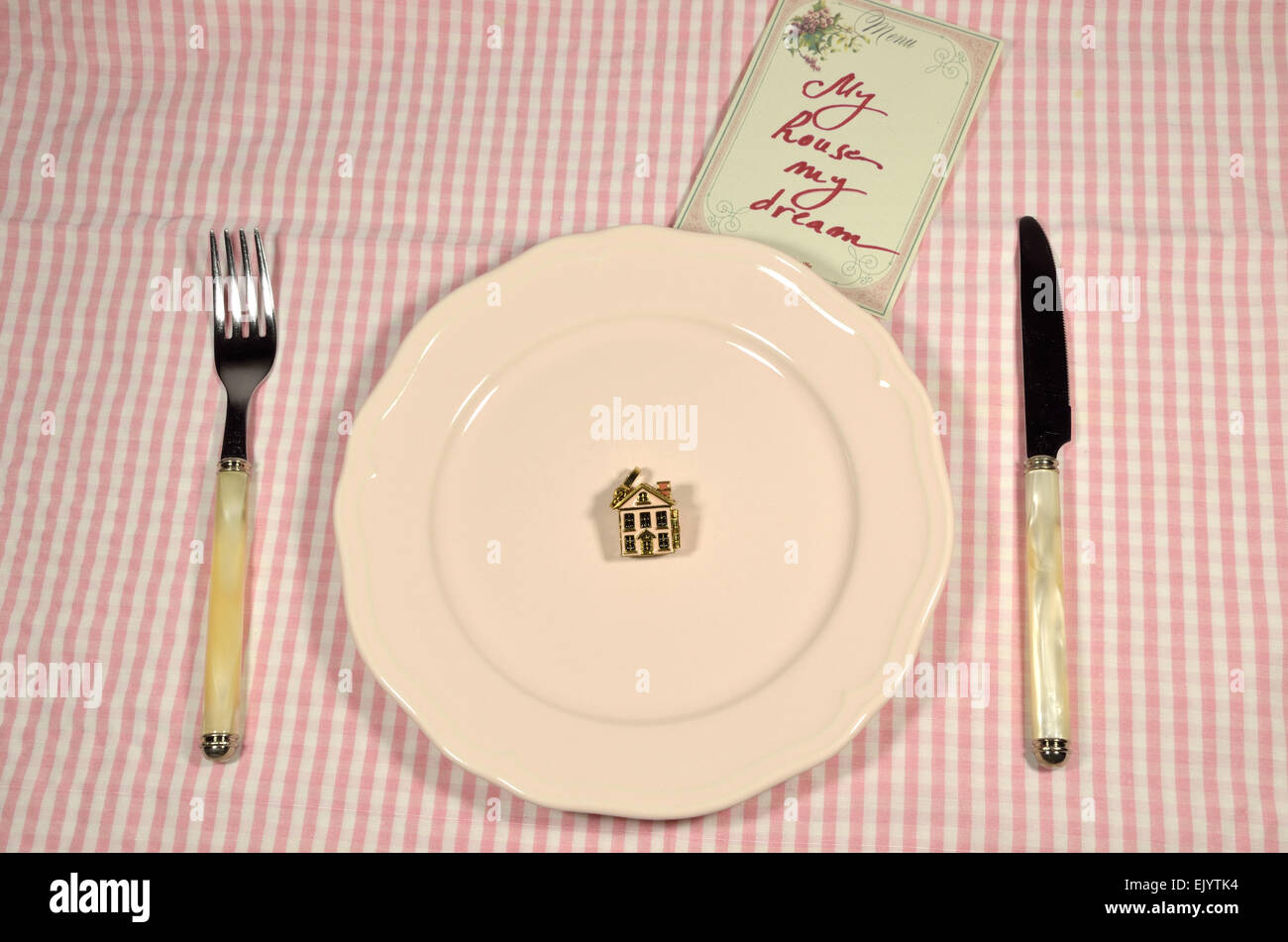 A small house served on a pink plate and a menu card. Scene is imagined as an  investment plan. Stock Photo