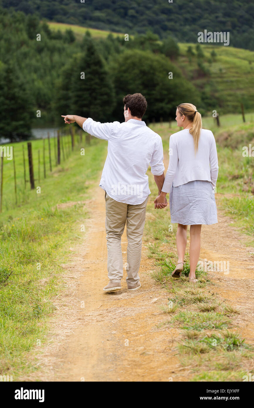 rear view of young couple walking in country road - Stock Image