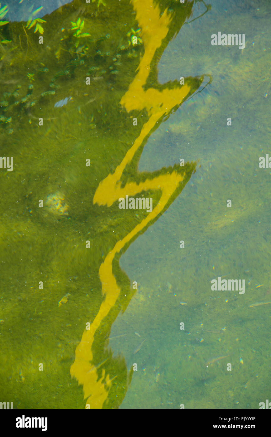reflection of a yellow line on a river surface - Stock Image